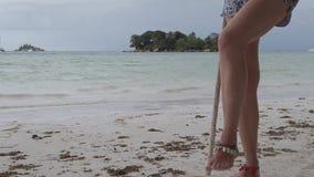 Swinging legs at Seychelles. Blonde woman swinging legs on beach swing Anse Volbert Cote d`Or, Praslin, Seychelles, Indian Ocean. Islet of Chauve Souris on stock footage