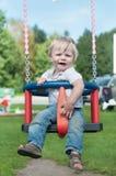 Swinging little boy in denim Royalty Free Stock Image