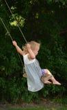 Swinging. Little girl swinging on tree rope swing Royalty Free Stock Photo