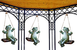 Swinging pergola frogs. Photo of garden frogs enjoying playing on their swings under a pergola Royalty Free Stock Photo