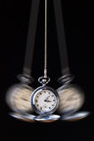 Swinging pocket watch hypnosis on black. Swinging pocket watch hypnosis on a black background royalty free stock image