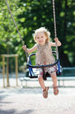 Swinging preschooler girl Stock Images