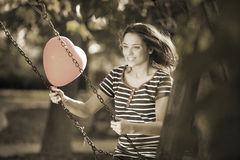 Swinging with a Red Shaped Heart Balloon. Happy Smiling Young Woman Swinging with a Red Shaped Heart Balloon Outdoors Royalty Free Stock Images