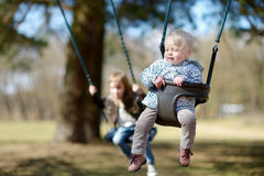 Swinging sisters having fun Royalty Free Stock Images