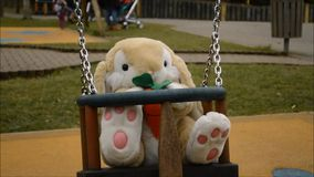 Swinging soft toy bunny stock footage