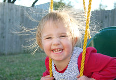 Swinging and Static Electricity. A little girl is swinging in her swing and her hair stands up from static electricity stock photo