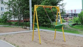 Swinging swing at playground near residential building stock video