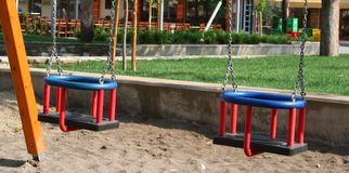 Swings. Little kids swings in a playground royalty free stock image