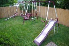 Swings. Purple swing set in a back yard Royalty Free Stock Photography