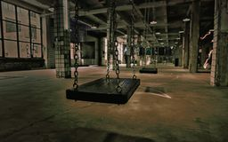 Swings in an abandoned old gloomy building with breakaway tiles Stock Images