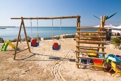 Swings on the beach Stock Photo