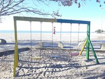 Swings on beach playground royalty free stock photography