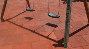 swings-casting-shadow-on-playground Stock Photography