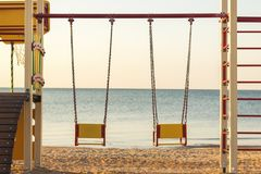 Two swings of children`s playgrounds on the beach. royalty free stock photo