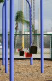 Swings in the City. A line of swings in a city playground Royalty Free Stock Image