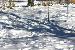 Swings covered in snow Stock Photography