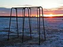 Swings on empty beach. Empty swings during sunset: quiet moods Royalty Free Stock Photos