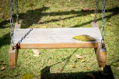 Swings in the garden with foliage on the lawn