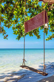Swings and palm on the sand tropical beach. Stock Photo
