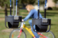 Swings at a park. Shot of a pair of swings with a woman riding a cycle in the background royalty free stock photo