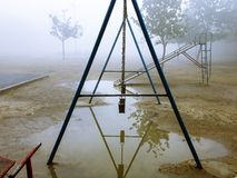 Swings in a park with rain water royalty free stock photos