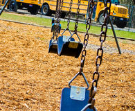 Swings on playground. Swings in school playground with buses in background Stock Photo