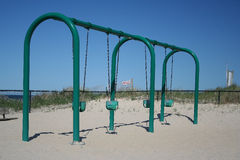 Swings on sandy beach. Row of swings on sandy beach with blue sky background Royalty Free Stock Photos