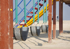 Swings in a sea beach at shallow depth of focus. Empty children swings in the sea beach royalty free stock image