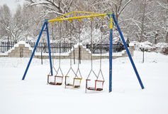 Swings with snow Stock Image