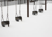 Swingset in Winter. A deserted swingset is almost buried in deep snow in the dead of winter Royalty Free Stock Photo