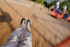 Swining feet. Feet on swing in motion in park royalty free stock photos