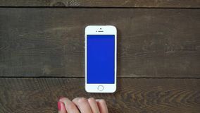 Swipes Left Hand Smartphone with Blue Screen. Female Hand Using Vertical Smartphone with Blue Screen Swipes Left on the Background of Wooden Table stock video