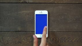 Swipes Left Hand Smartphone with Blue Screen. Man Hand Using Vertical Smartphone with Blue Screen Swipes Left on the Background of Wooden Table stock footage