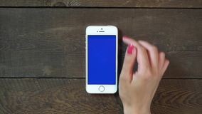 Swipes Up Hand Smartphone with Blue Screen. Female Hand Using Vertical Smartphone with Blue Screen Swipes Up on the Background of Wooden Table stock footage