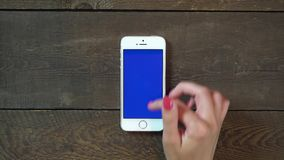 Swipes Up Hand Smartphone with Blue Screen. Female Hand Using Vertical Smartphone with Blue Screen Swipes Up on the Background of Wooden Table stock video footage