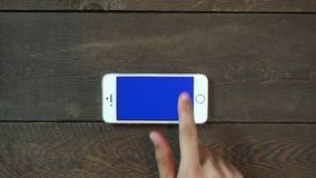 Swipes Up Hand Smartphone with Blue Screen stock footage
