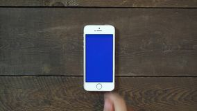 Swipes Up Hand Smartphone with Blue Screen. Man Hand Using Vertical Smartphone with Blue Screen Swipes Up on the Background of Wooden Table stock video footage