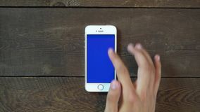 Swipes Up Hand Smartphone with Blue Screen. Man Hand Using Vertical Smartphone with Blue Screen Swipes Up on the Background of Wooden Table stock footage