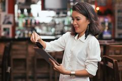 Swiping card payment. Bar owner using credit card reader on the tablet to swipe payment Royalty Free Stock Photo