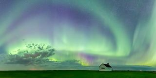 Swirl of Aurora Borealis Northern Lights over the historical North Saskatchewan Landing school. Established in 1914 near Kyle, Saskatchewan, Canada stock photography