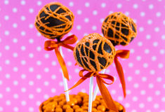 Swirl Cake Pops. Chocolate cake pops with orange swirl glitter sugar decorations against pink polka dot background Royalty Free Stock Images