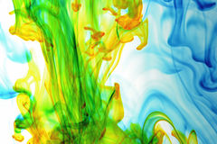 Swirl II. Color photo of blue, green, and yellow food coloring swirling and mixing in water with white background Royalty Free Stock Image