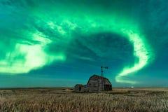 Swirl of Northern Lights over vintage barn in Saskatchewan, Canada royalty free stock image