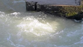 Swirl of water near the town bridge supports. Urban water gateway. Real time stock video