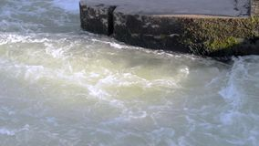 Swirl of water near the town bridge supports. Urban water gateway. Slowly 50 stock footage