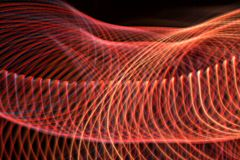 Swirl and waves of red lights with some blue with a black background. Lines intersecting, dark red and bright red Stock Photography