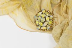 Swirled sheer yellow floral scarf with a vintage cabochon and rhinestone brooch on white. Horizontal aspect Royalty Free Stock Photo