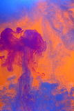Swirling abstract clouds. An abstract cloud of violet, blue and purple paint against an orange background Royalty Free Stock Image