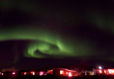 Swirling Aurora Borealis over a Small Town in North Iceland royalty free stock image