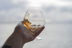Swirling brandy in glass. Snifter with brandy swirling in hand close up view royalty free stock photos